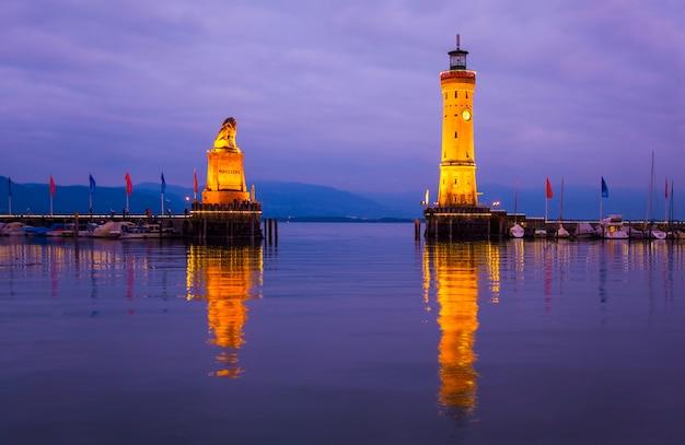 Wejście do portu nad jeziorem bodeńskim. widok starej latarni morskiej i posąg lwa przy wejściu do portu w lindau o zachodzie słońca