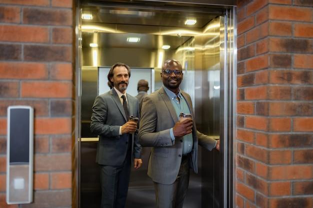 Wejście do windy. dwóch zamożnych biznesmenów wchodzących rano do windy z kawą na wynos