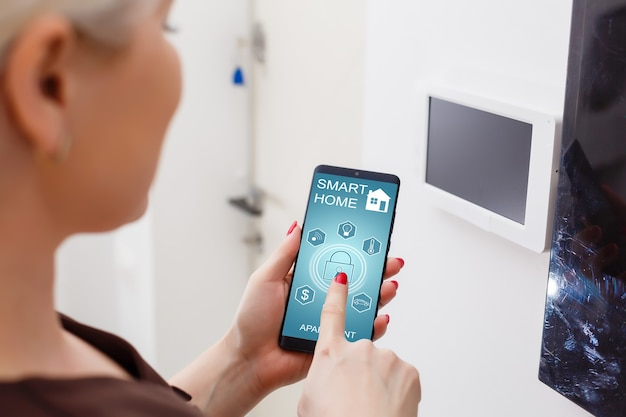 Wejście hasła inteligentnej klawiatury domowej. ludzka ręka naciskając kombinację kodu zabezpieczającego, aby odblokować drzwi. personel naciska przycisk systemu kontroli dostępu, aby odblokować drzwi. selektywne skupienie.