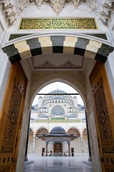 Wejście na wewnętrzny dziedziniec meczetu camlica z ludźmi w środku, biały marmur, stambuł, turcja