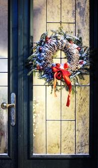 Wejście ozdobione domowym wieńcem bożonarodzeniowym