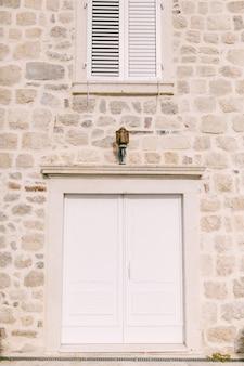 Wejście przez białe podwójne drzwi pod latarnią
