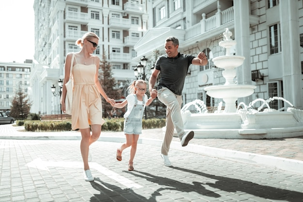 Wejście w drugie dzieciństwo. szczęśliwa mała dziewczynka i jej troskliwi rodzice trzymając się za ręce i przeskakując ulicą miasta.