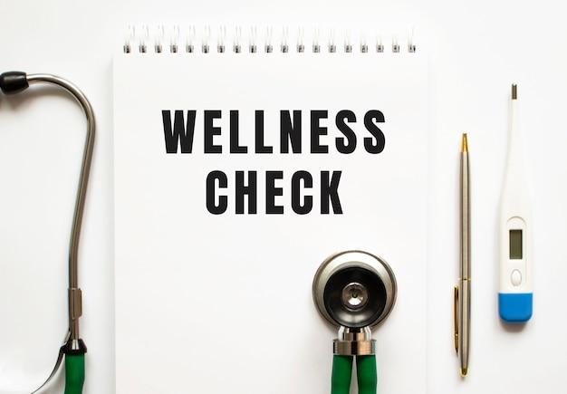 Wellness check tekst zapisany w notesie leżącym na biurku i stetoskopie