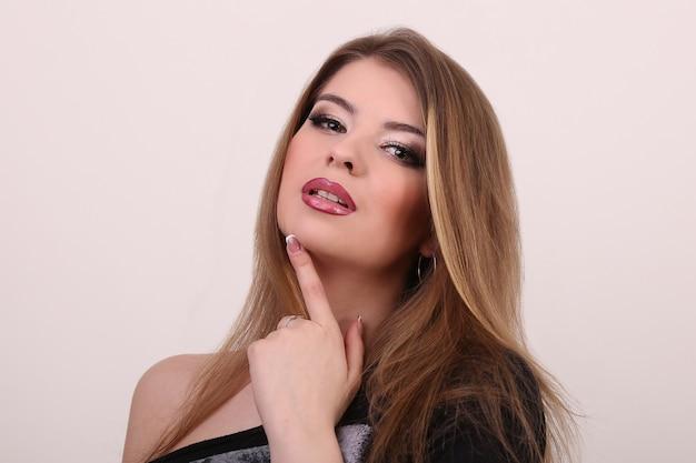 Wellness i spa. zmysłowy model kobiety z smagane wiatrem włosy latające brunetki na jasnoszarej ścianie. błyszcząca długa fryzura zdrowotna. uroda i pielęgnacja włosów. naturalny makijaż