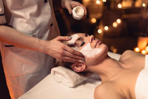 Wellness pojęcie z kobietą z creme w twarzy