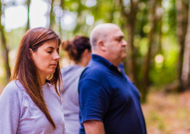Wellness warsztaty medytacji latynoska grupa dorosłych relaksuje się razem z oczami zamkniętymi w leśnym oddechu...