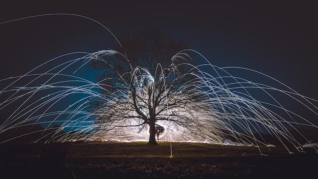 Wełna stalowa wirująca nocą nad ziemią w pobliżu drzewa