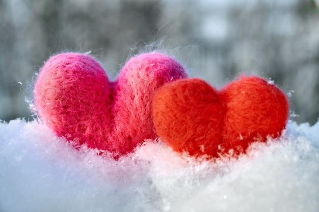 Wełniane czerwono-różowe serduszka na białym puszystym śniegu zimą. symbole miłości.