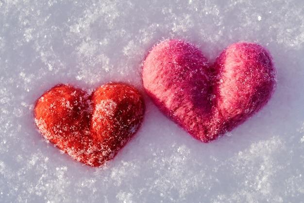 Wełniane serca leżały zimą na białym puszystym śniegu. koncepcja walentynki.