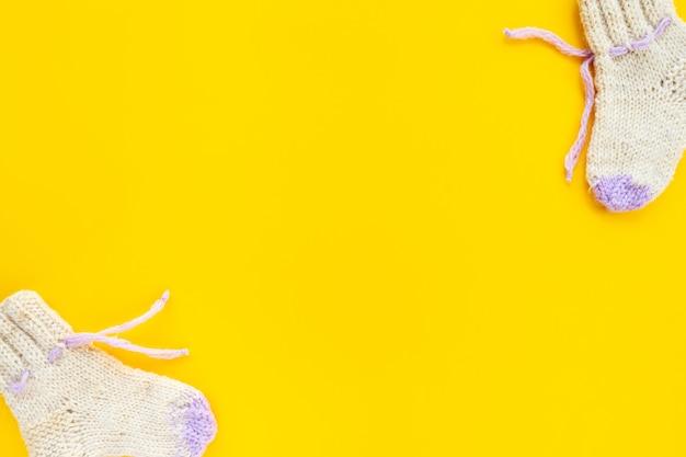 Wełniane skarpetki dziecięce z dzianiny na żółtym tle, płaskie płaskie, widok z góry, kopia przestrzeń. koncepcja dziecka. minimalistyczne tło dla noworodków dla dziewczynek.