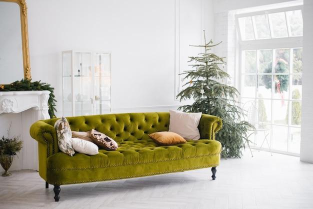 Welurowa sofa z poduszkami w jasnym pokoju