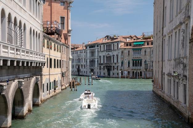 Wenecja, włochy - 1 lipca 2018: panoramiczny widok na wąski kanał wenecji z zabytkowymi budynkami i ruchem łodzi z mostu foscari. krajobraz letniego słonecznego dnia i błękitnego nieba