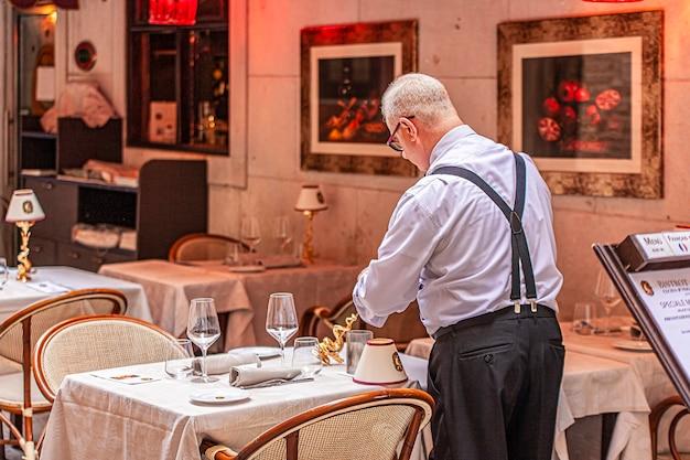 Wenecja, włochy 2 lipca 2020: kelner przygotowuje stół