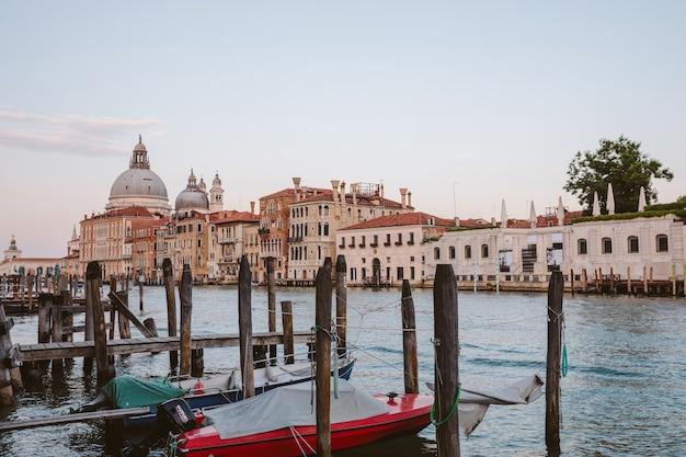 Wenecja, włochy - 30 czerwca 2018 r.: panoramiczny widok z wenecji grand canal z zabytkowymi budynkami i łodziami, z dala od bazyliki salute. krajobraz letniego wieczoru i kolorowe niebo