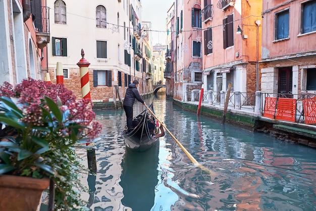 Wenecja włochy gondolier jeździ gondolą przez wąski kanał między kolorowymi domami