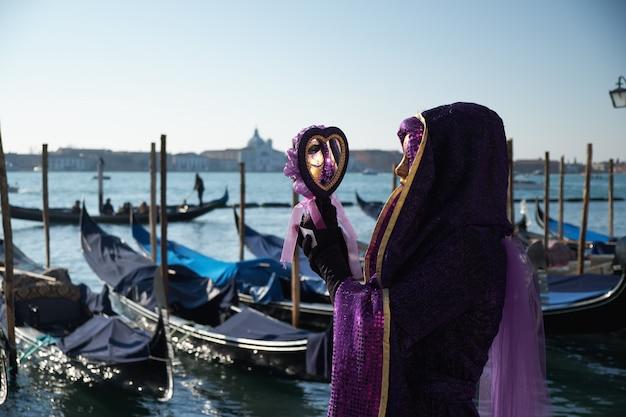 Wenecja, włochy. kobieta w masce i kostiumu przy wenecja karnawałem
