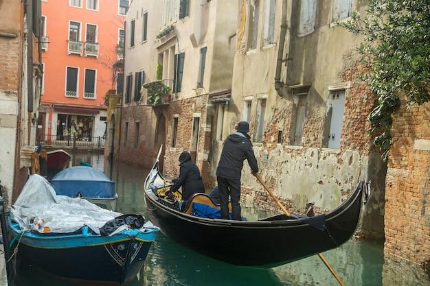 Wenecja włochy, listopad, - 7,2016: widok gondolowej łodzi usługowej klientowi i turystyczni ludzie w wenecji rzece i kanale, włochy.
