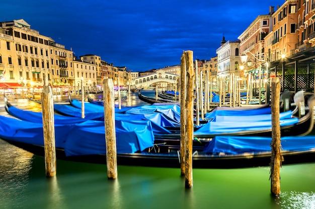 Wenecja, włochy. most rialto i canal grande o zmierzchu w niebieskiej godzinie. gondole na pierwszym planie.