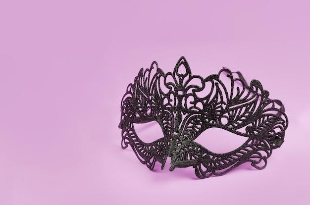 Wenecka delikatna czarna maska na różowym tle.