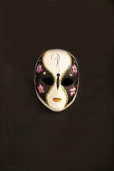Wenecka maska karnawałowa pośrodku czarnego tła. widok z góry. skopiuj miejsce. lokalizacja w pionie.
