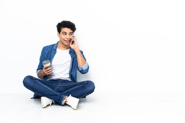 Wenezuelczyk siedzi na podłodze i trzyma kawę na wynos i telefon komórkowy