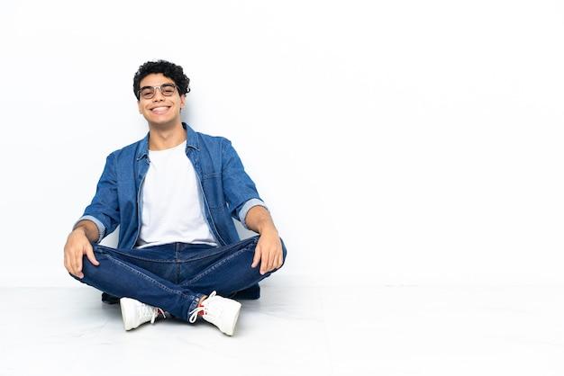 Wenezuelczyk siedzi na podłodze w okularach i szczęśliwy