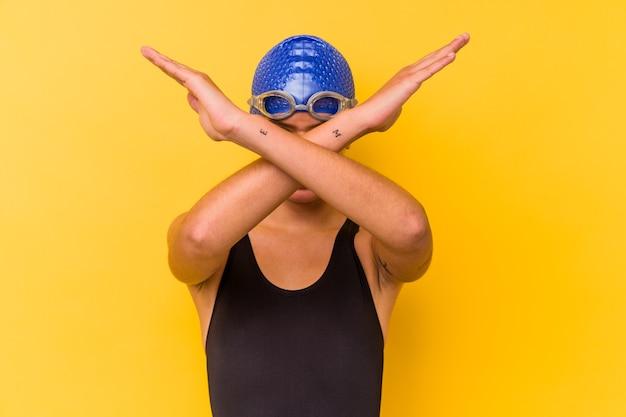 Wenezuelska kobieta młody pływak na białym tle na żółtym tle trzymając dwa ramiona skrzyżowane, koncepcja odmowa.