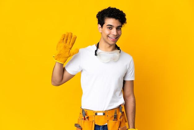 Wenezuelski elektryk mężczyzna na żółtym pozdrawiając ręką z szczęśliwy wyraz