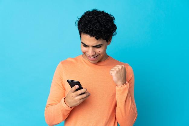 Wenezuelski mężczyzna na białym tle na niebiesko za pomocą telefonu komórkowego i robi gest zwycięstwa