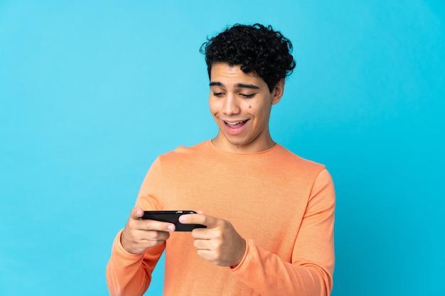 Wenezuelski mężczyzna na niebieskim tle, grając z telefonem komórkowym