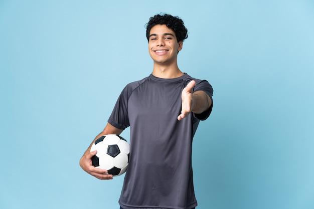 Wenezuelski piłkarz mężczyzna na białym tle ściskając ręce za zamknięcie dobrego interesu
