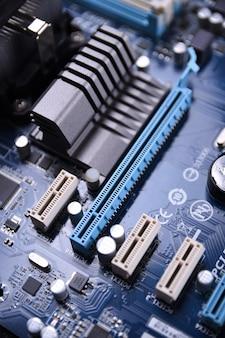 Wentylator komputera na płycie głównej i komponentach elektronicznych pamięć procesora gpu i różne gniazda na kartę graficzną z bliska
