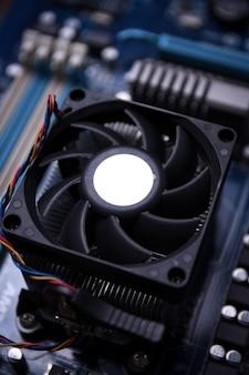 Wentylator komputera na płycie głównej i komponentach elektronicznych pamięć procesora gpu oraz różne gniazda do kart graficznych z bliska