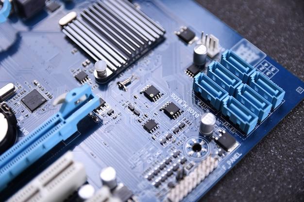 Wentylator komputera na płycie głównej i podzespoły elektroniczne cpu pamięć gpu i różne gniazda karty graficznej z bliska