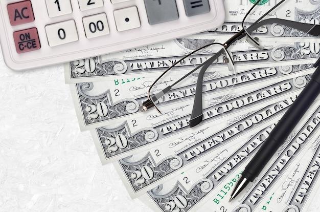Wentylator rachunki w dolarach amerykańskich i kalkulator z okularami i długopisem