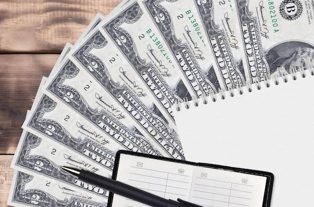 Wentylator rachunki w dolarach amerykańskich i notatnik z książką kontaktową i czarnym piórem