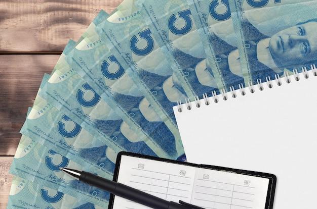 Wentylator rachunki w dolarach kanadyjskich i notatnik z książką kontaktową i czarnym długopisem