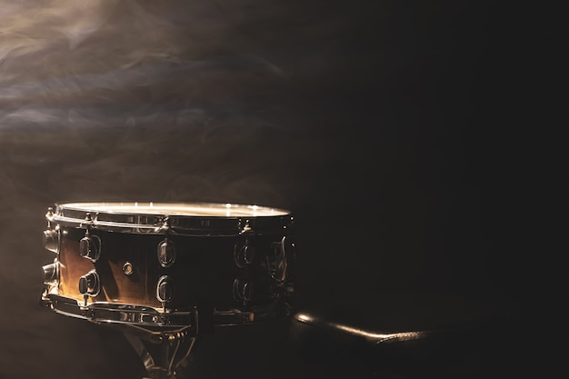 Werbel na czarnym tle, instrument perkusyjny w ciemności z dymem scenicznym, kopia przestrzeń.