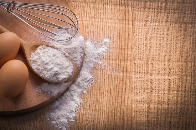 Wersja pionowa widok z lotu ptaka dwa jajka mąki łyżki corolla na drewnianym stole