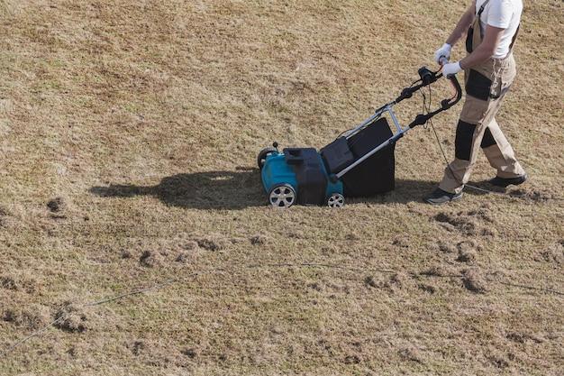 Wertykulacja trawnika za pomocą wertykulatora, ogrodnik man wertykuluje trawnik i usuwa starą trawę