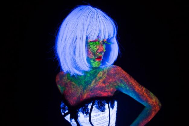Wesele w neonowym świetle w modnym stylu panna młoda świeci w ciemności młoda dziewczyna z quadami fryzjerskimi i bukietem pozuje w białej sukni ślubnej pod promieniami uv na ciemnym tle w studio
