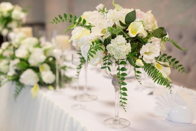 Wesele wystrój we wnętrzu, białe kwiaty na stole, serwująca stół z kryształowymi szklankami.