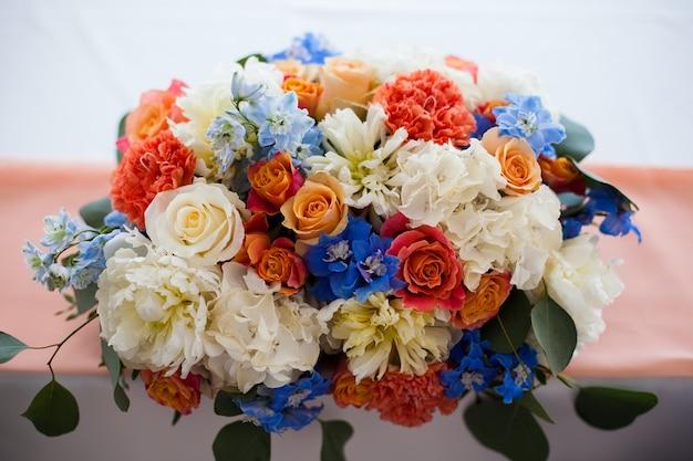 Weselne nakrycie z kwiatami w kolorze niebieskim, białym, czerwonym