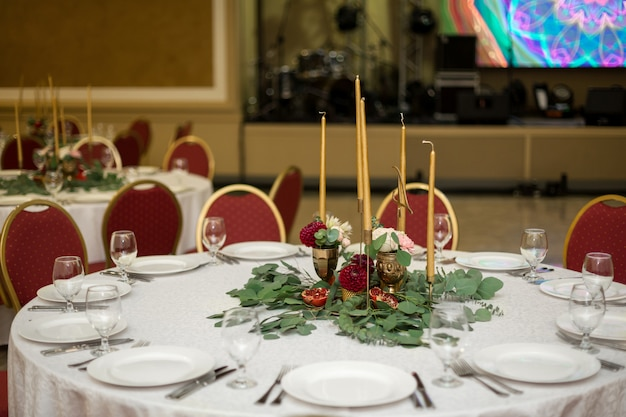 Weselne nakrycie zdobią świeże kwiaty w mosiężnej misce i złote świece w mosiężnych świecznikach