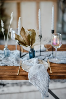 Weselny bankiet. świąteczna dekoracja w jasnych kolorach. drewniany stół podany ze sztućcami, świecami, suszonymi kwiatami i lnianym błękitnym bieżnikiem