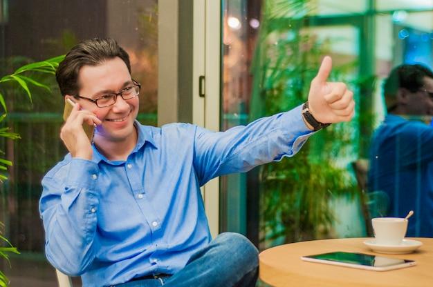 Weso? a zrelaksowany m? ody biznesmen pokazano ok gest i rozmawia? na telefon komórkowy w kawiarni