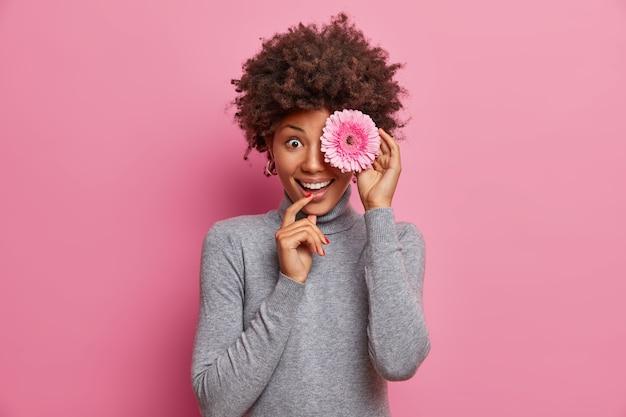 Wesoła afro amerykanka zakrywa oko śliczną gerberą, szczerze się uśmiecha, stoi rozbawiona, ubrana w luźny poloneck