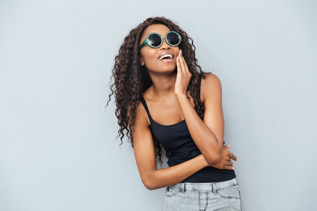 Wesoła afro kobieta w okularach pozuje na szarej ścianie