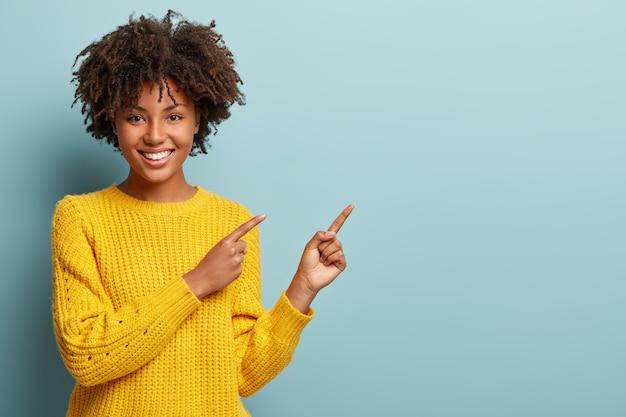 Wesoła afro kobieta wskazuje na przestrzeń kopii, ustępuje lub kieruje, nosi żółty ciepły sweter, ma przyjemny uśmiech, czuje się optymistycznie, odizolowana na niebieskim tle